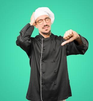 Grave jovem chef fazendo um gesto de derrotado