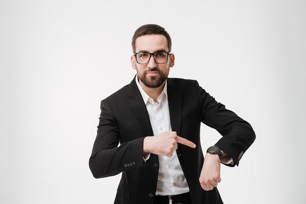 Grave jovem empresário barbudo mostrando o relógio.