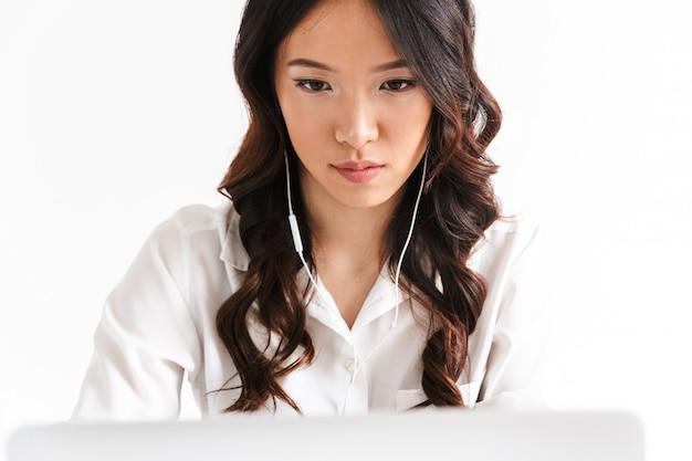 Grave mulher asiática vestindo roupas de escritório e fones de ouvido sentado à mesa e olhando para laptop