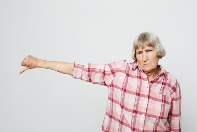Grave mulher envelhecida, apontando o dedo para baixo. retrato de avó expressiva com camisa rosa.