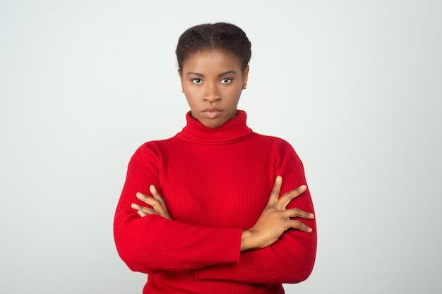 Grave mulher estrita, vestindo blusa vermelha