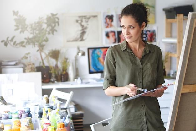 Grave pintor feminino atraente, com cabelos escuros, camisa casual, em pé em sua oficina, segurando o pincel nas mãos, usando aquarelas para pintar imagens. pintura de pessoa criativa