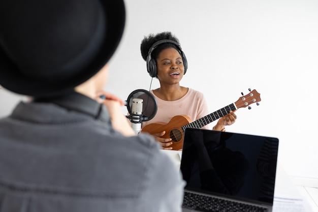 Grave um podcast e crie conteúdo de áudio de uma mulher afro-americana tocando ukulele em uma gravação