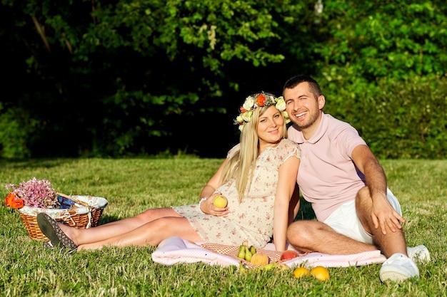 Grávida casal no parque natural em um piquenique no verão