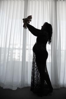 Grávida com vestido de renda preta contra luz