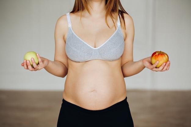 Grávida de maçãs. duas maçãs na palma da mulher grávida.