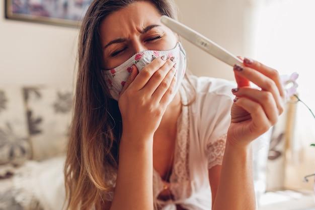 Grávida durante o coronavírus covid-19. mulher doente na máscara, verificando a tosse do teste de gravidez.