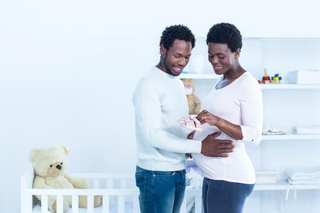 Grávida mostrando sapatos de bebê para o marido