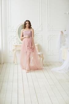 Grávida mulher encaracolada em rosa