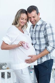 Grávida, par, segurando, bebê, sapatos, lar