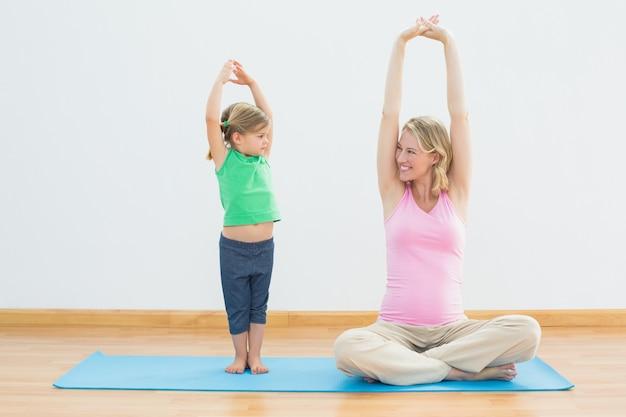 Grávida sorrindo mãe e filha fazendo ioga juntos