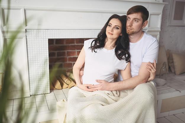 Gravidez e conceito de pessoas. homem feliz, abraçando sua linda esposa grávida em casa. futuros pais esperando bebê por nascer.