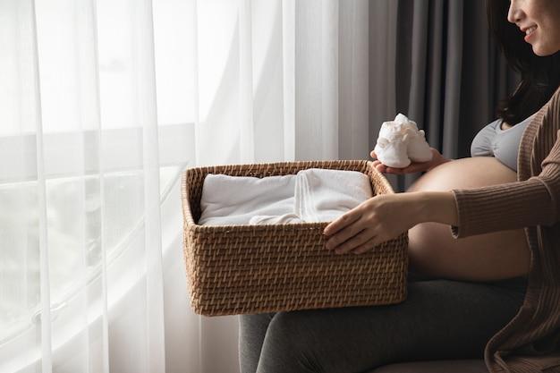 Gravidez, maternidade e conceito da expectativa - mulher gravida que prepara sapatas vestidas e pequenas para o bebê por nascer.