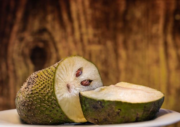 Graviola frutas fatiadas perto fundo de madeira