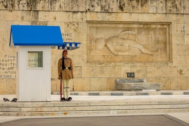 Grécia, atenas. túmulo de soldado desconhecido. soldado com roupas históricas em pé no posto com um rifle