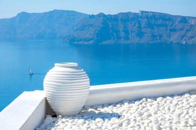Grécia. dia de sol em santorini. seixos brancos e um vaso de pedra. vista do mar com ilhas rochosas