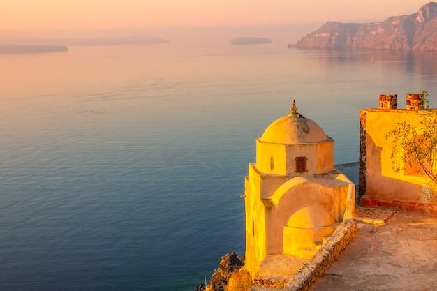 Grécia. ilha de santorini ao pôr do sol. antiga igreja grega em oia