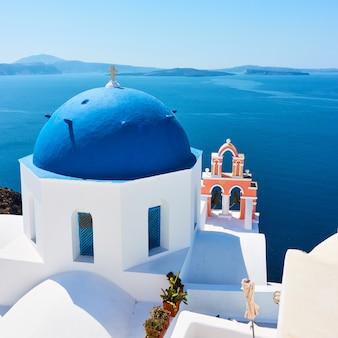 Grécia, ilha de santorini. vista panorâmica com igreja branca à beira-mar em oia. paisagem grega