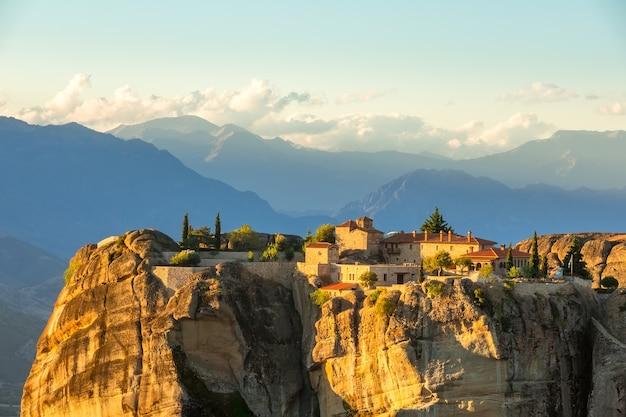 Grécia. pôr do sol de verão em meteora. mosteiro de rocha em um fundo de nuvens sobre os picos das montanhas