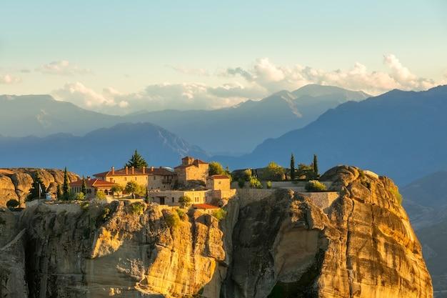 Grécia. pôr do sol de verão em meteora. mosteiro de rocha no fundo de picos de montanhas