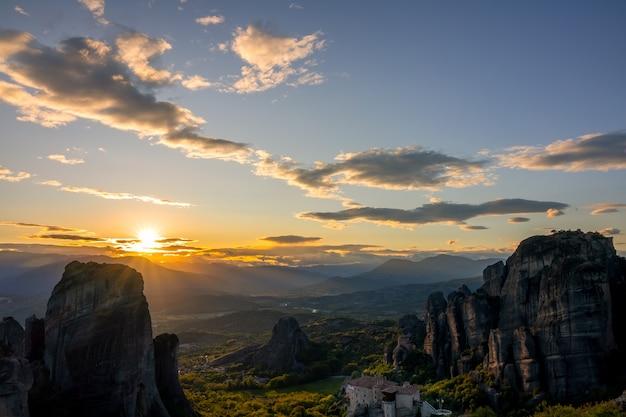 Grécia. pôr do sol de verão sobre o vale dos mosteiros rochosos em meteora (perto de kalambaka) e raios de sol