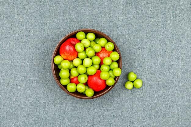 Greengages e pêssegos em uma tigela de barro marrom no cinza. vista do topo.