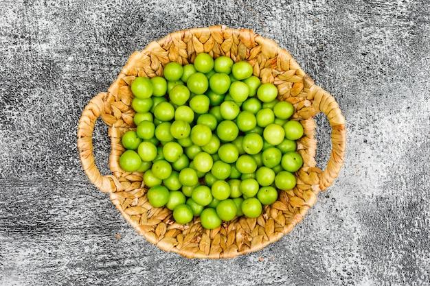 Greengages saborosos em uma cesta de vime na superfície do grunge, vista superior.