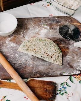 Greenies qutab verdes ervas massa cozinhar na mesa rústica de madeira marrom