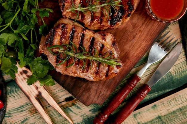 Grelha de carne de porco bife na tábua de madeira