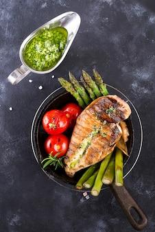 Grelha de peito de frango com churrasco legumes e molho pesto em uma panela de ferro fundido em uma pedra