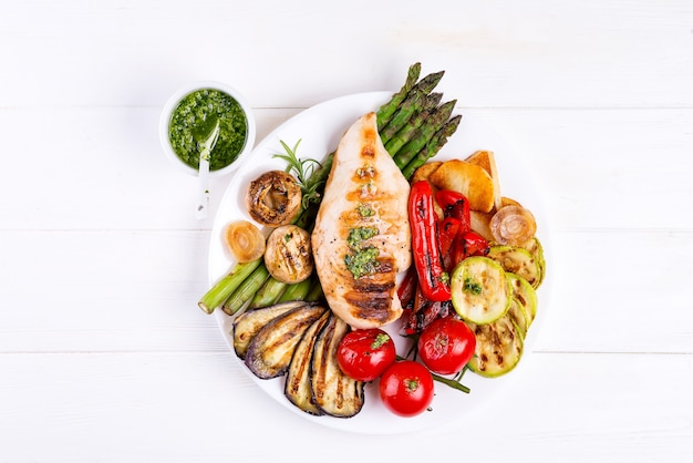 Grelha de peito de frango com legumes para churrasco e molho pesto em um prato na madeira