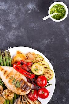 Grelha de peito de frango com legumes para churrasco e molho pesto em uma panela de ferro fundido