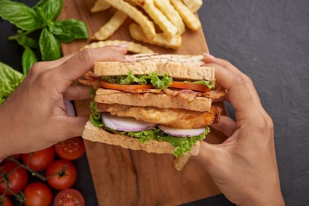 Grelhado e sanduíche com bacon, ovo frito, tomate e alface servido em tábua de madeira
