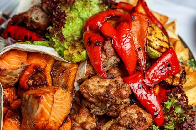 Grelhados de carne grelhada, legumes fritos e decoração de filetes de peixe salmão grelhado em prato quente