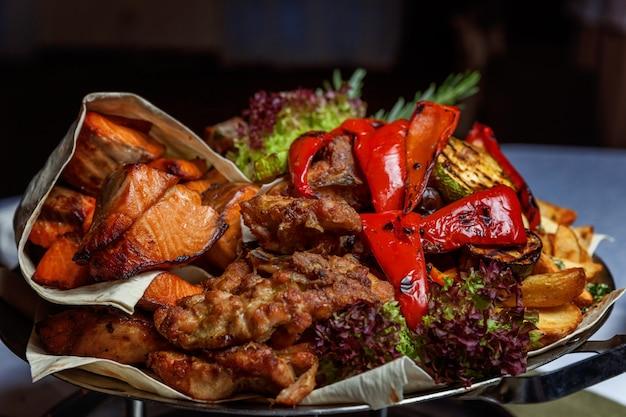 Grelhados de carne, legumes fritos e decoração de filetes de peixe salmão grelhado em prato quente