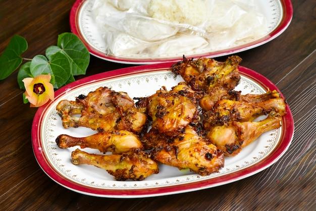 Grelhe a galinha com o arroz pegajoso no prato.