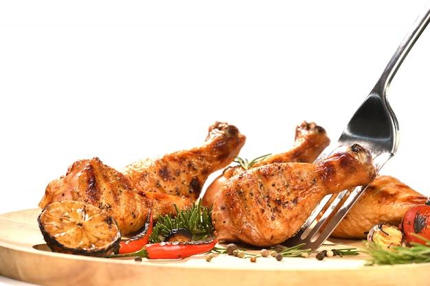 Grelhe a perna de frango do assado e o vegetal do assado isolados no fundo branco