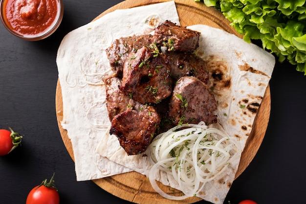 Grelhe, carne de churrasco na placa de madeira. espetinho de vitela. kebab de vitela. vista do topo