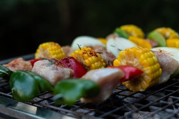 Grelhe espetos de carne e vegetais em enorme no braseiro. conceito de cozinhar carne no churrasco