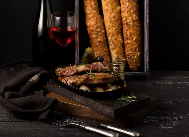 Grelhe o bife de porco em uma tábua de madeira rústica velha em uma cozinha de país com vinho tinto e baguete francesa na parede preta de madeira