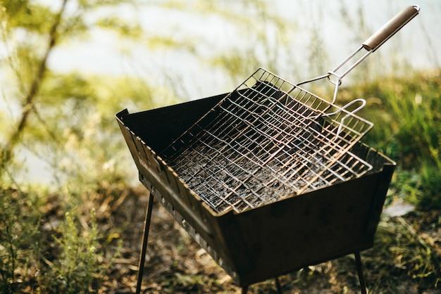 Grelhe para fritar fica à beira de um penhasco em um dia ensolarado. cozinhando para o fogo. fogo seguro sobre a natureza no churrasco. tudo para um piquenique.