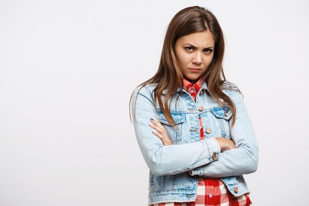 Gril engraçado triste na jaqueta jeans com os braços do outro lado