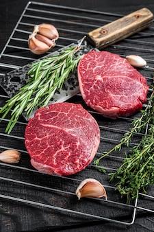 Grill bbq - bifes de carne crua de filé mignon com ervas. fundo de madeira preto. vista do topo.