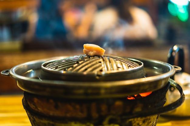Grill óleo de porco em uma panela para iniciar o cozinheiro, comida tailandesa