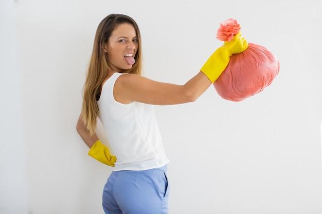 Grimacing girl com saco de lixo esticando a língua