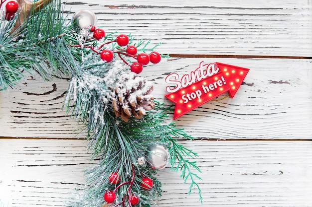 Grinalda agradável do natal com bagas e o pinecone vermelhos na madeira. decoração de natal em casa. cartão de ano novo. feliz natal e feliz ano novo conceito de férias em família. seta vermelha com a palavra santa