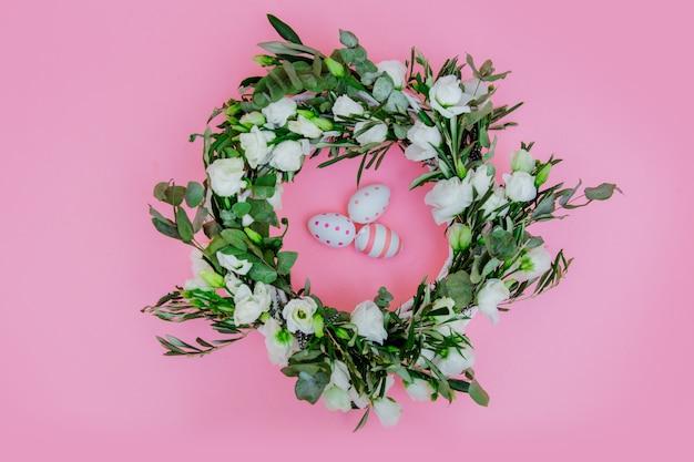 Grinalda com rosas brancas e ovos de páscoa em fundo rosa. decorado. acima vista