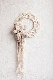 Grinalda de macramê com uma flor grande de algodão em uma parede de gesso decorativo