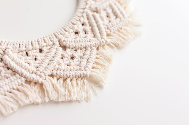 Grinalda de macrame em uma superfície branca close-up. fio de algodão natural. eco decoração da casa. copie o espaço