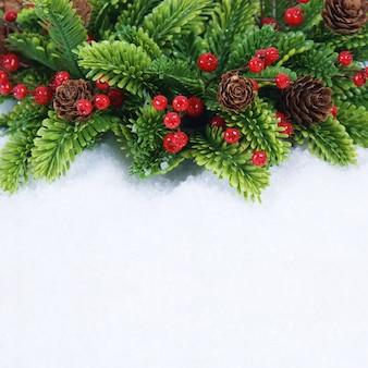 Grinalda de natal com cones de pinheiro e bagas aninhadas na neve